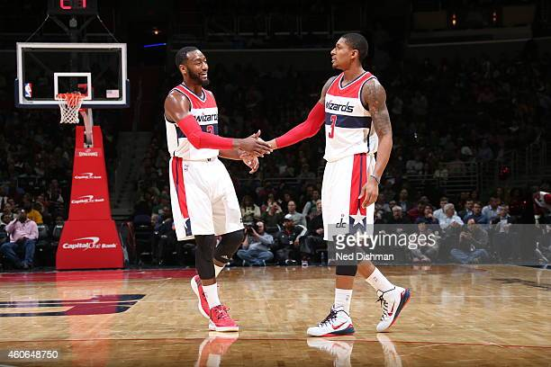 John Wall and Bradley Beal of the Washington Wizards celebrate during a game against the Boston Celtics on December 8 2014 at the Verizon Center in...
