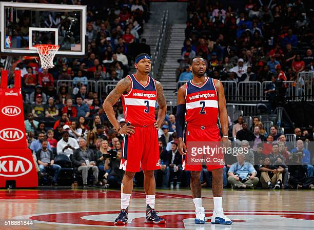 John Wall and Bradley Beal of the Washington Wizards look on during free throws against the Atlanta Hawks at Philips Arena on March 21 2016 in...