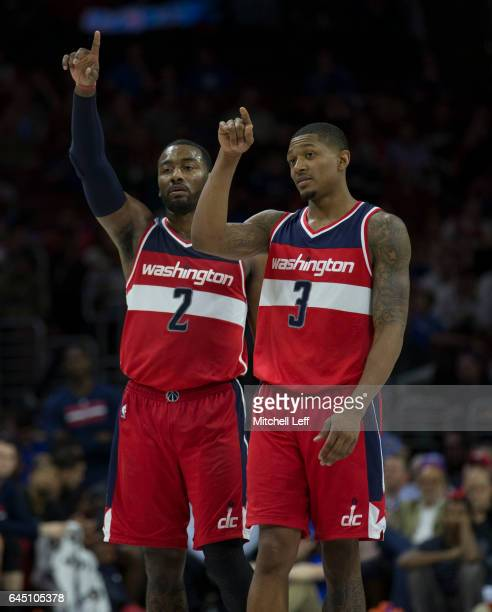 John Wall and Bradley Beal of the Washington Wizards point in the fourth quarter against the Philadelphia 76ers at the Wells Fargo Center on February...
