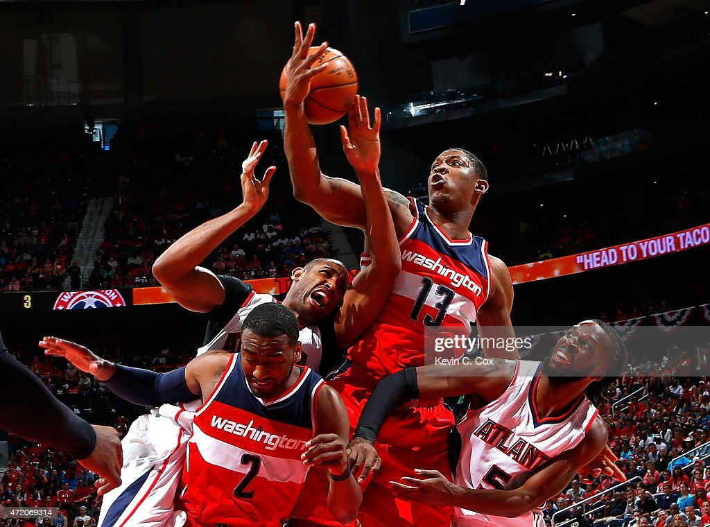 John Wall #2 and Kevin Seraphin #13 of the Washington Wizards defend as Al Horford #15 of the Atlanta Hawks attempts a shot during Game One of the Eastern Conference Semifinals of the 2015 NBA Playoffs at Philips Arena on May 3, 2015 in Atlanta, Georgia.