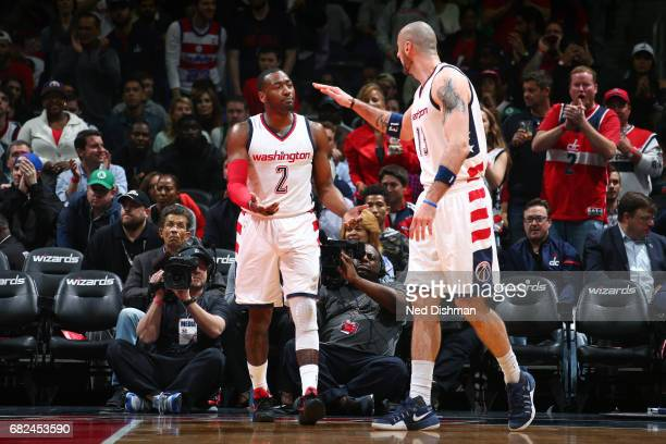 John Wall and Marcin Gortat of the Washington Wizards high five each other during the game against the Boston Celtics during Game Six of the Eastern...