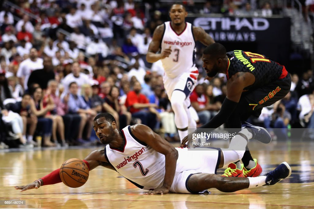 John Wall #2 of the Washington Wizards and Tim Hardaway Jr. #10 of the Atlanta Hawks go after a loose ball in the first half of Game One of the Eastern Conference Quarterfinals during the 2017 NBA Playoffs at Verizon Center on April 16, 2017 in Washington, DC.