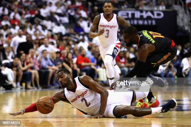 John Wall of the Washington Wizards and Tim Hardaway Jr #10 of the Atlanta Hawks go after a loose ball in the first half of Game One of the Eastern...