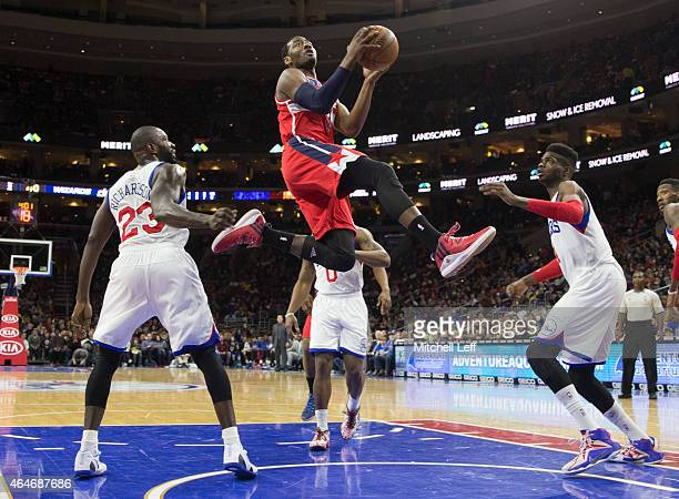 John Wall of the Washington Wizards attempts a layup with Jason Richardson and Nerlens Noel of the Philadelphia 76ers defending on the play on...