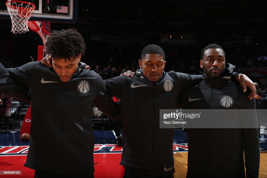 John Wall #2 of the Washington Wizards Bradley Beal #3 of the Washington Wizards and Kelly Oubre Jr. #12 of the Washington Wizards during the national antem before the game against the Memphis Grizzlies on December 13, 2017 at Capital One Arena in Washington, DC.