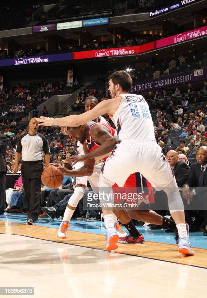 John Wall of the Washington Wizards drives against Byron Mullens of the Charlotte Bobcats at the Time Warner Cable Arena on March 18 2013 in...