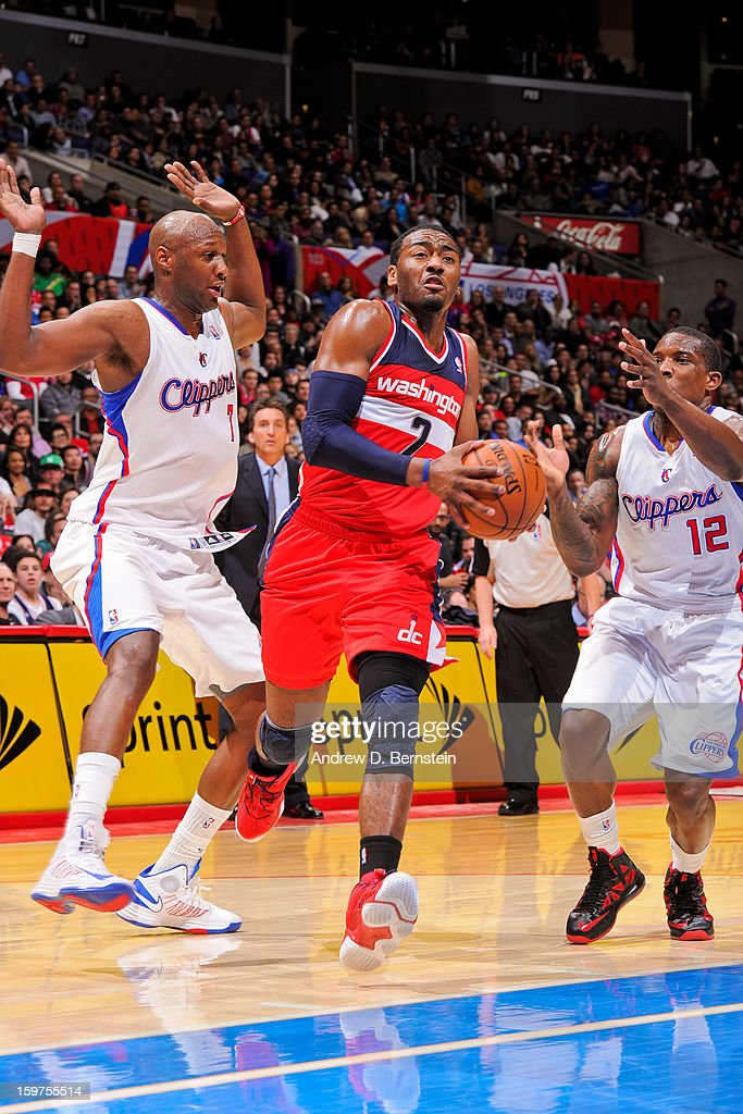 John Wall #2 of the Washington Wizards drives to the basket against Lamar Odom #7 and Eric Bledsoe #12 of the Los Angeles Clippers at Staples Center on January 19, 2013 in Los Angeles, California.