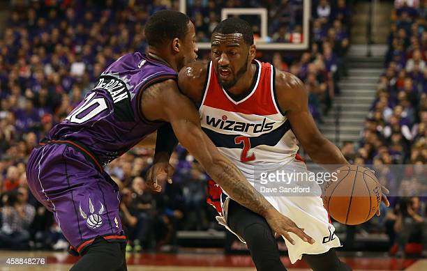 John Wall of the Washington Wizards drives to the basket as DeMar DeRozan of the Toronto Raptors defends during their NBA game at the Air Canada...