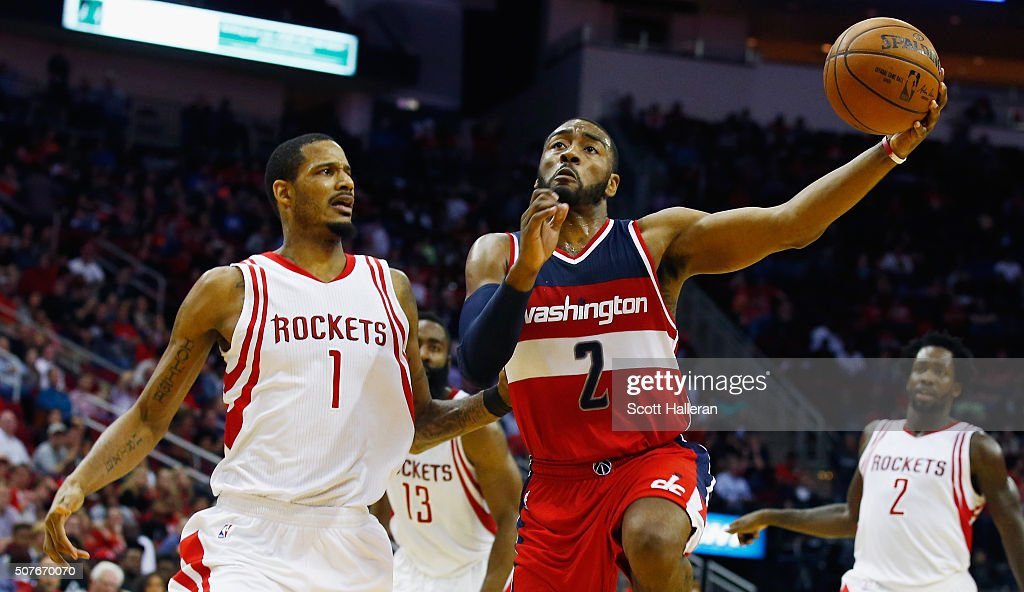 John Wall of the Washington Wizards drives with the basketball against Trevor Ariza of the Houston Rockets during their game at the Toyota Center on...