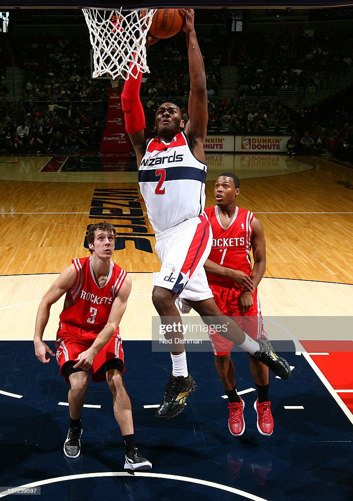 John Wall #2 of the Washington Wizards dunks against <a gi-track='captionPersonalityLinkClicked' href=/galleries/search?phrase=Goran+Dragic&family=editorial&specificpeople=4452965 ng-click='$event.stopPropagation()'>Goran Dragic</a> #3 and Kyle Lowry #7 of the Houston Rockets during the game at the Verizon Center on January 16, 2012 in Washington, DC.