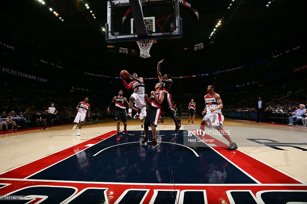 <a gi-track='captionPersonalityLinkClicked' href=/galleries/search?phrase=John+Wall&family=editorial&specificpeople=2265812 ng-click='$event.stopPropagation()'>John Wall</a> #2 of the Washington Wizards goes to the basket against <a gi-track='captionPersonalityLinkClicked' href=/galleries/search?phrase=Gerald+Wallace&family=editorial&specificpeople=202117 ng-click='$event.stopPropagation()'>Gerald Wallace</a> #3 and Joel Przybilla #10 of the Portland Trail Blazers at the Verizon Center on March 10, 2012 in Washington, DC.