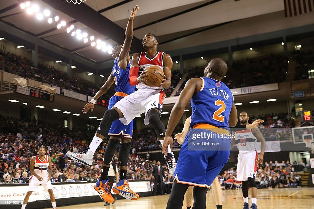 John Wall #2 of the Washington Wizards goes to the basket against Tim Hardaway Jr. #5 of the New York Knicks during the pre-season game at the Baltimore Arena on October 17, 2013 in Baltimore, MD.