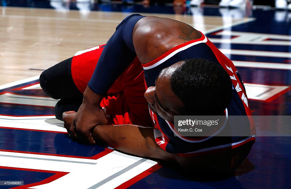 John Wall #2 of the Washington Wizards grabs his wrist after missing a basket and landing on the floor against the Atlanta Hawks during Game One of the Eastern Conference Semifinals of the 2015 NBA Playoffs at Philips Arena on May 3, 2015 in Atlanta, Georgia.