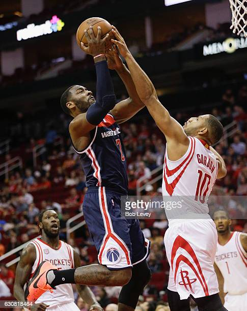 John Wall of the Washington Wizards has his shot blocked by Eric Gordon of the Houston Rockets as he drives to the basket in the second half at...