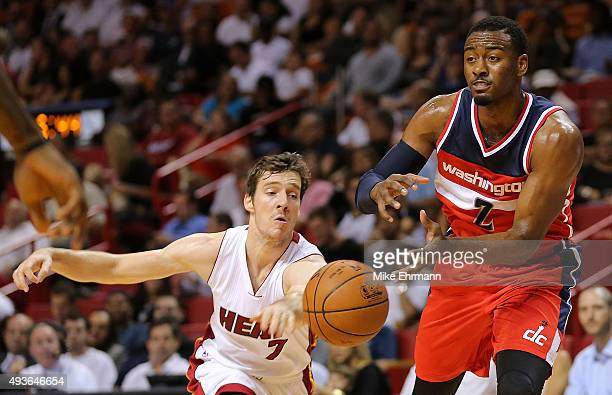John Wall of the Washington Wizards has the ball poked aways by Goran Dragic of the Miami Heat during a preseason game at American Airlines Arena on...