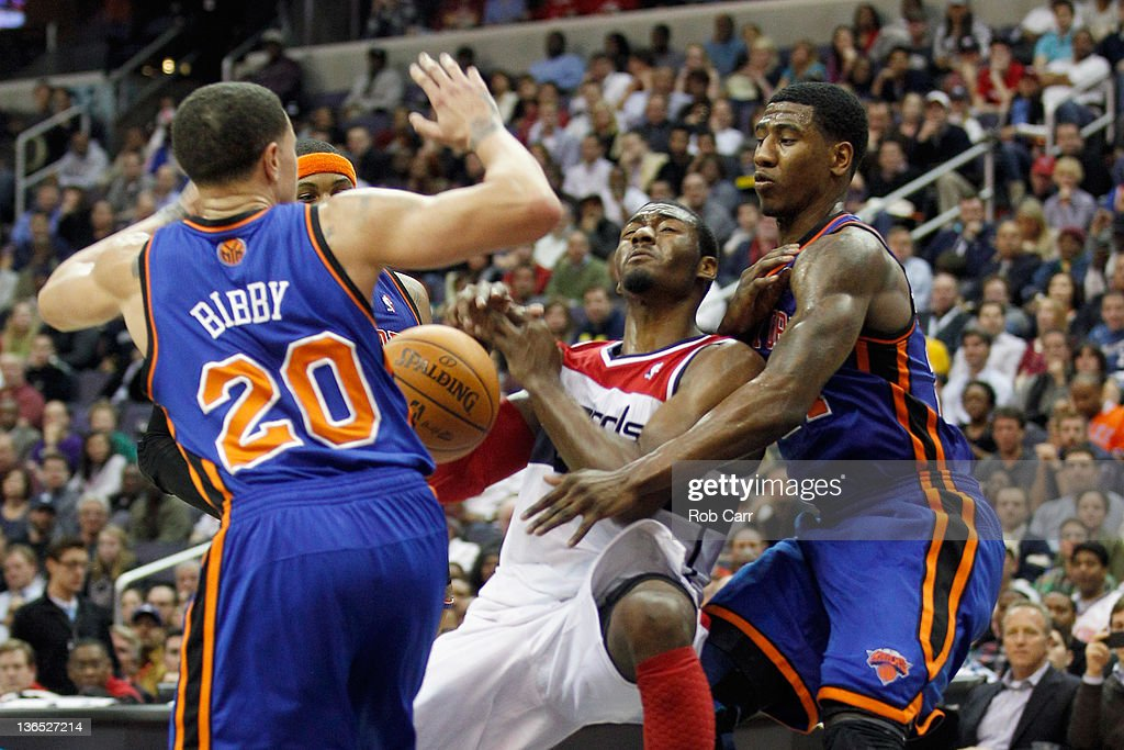 <a gi-track='captionPersonalityLinkClicked' href=/galleries/search?phrase=John+Wall&family=editorial&specificpeople=2265812 ng-click='$event.stopPropagation()'>John Wall</a> #2 of the Washington Wizards losses control of the ball while being guarded by <a gi-track='captionPersonalityLinkClicked' href=/galleries/search?phrase=Mike+Bibby&family=editorial&specificpeople=201503 ng-click='$event.stopPropagation()'>Mike Bibby</a> #20 and <a gi-track='captionPersonalityLinkClicked' href=/galleries/search?phrase=Iman+Shumpert&family=editorial&specificpeople=5042486 ng-click='$event.stopPropagation()'>Iman Shumpert</a> #21 of the New York Knicks during the second half at Verizon Center on January 6, 2012 in Washington, DC.