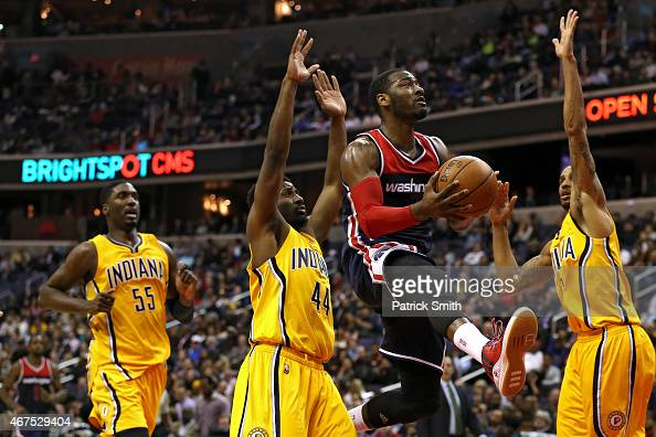 John Wall of the Washington Wizards puts up a shot between Solomon Hill and George Hill of the Indiana Pacers in the first half at Verizon Center on...