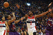 John Wall of the Washington Wizards reaches for a loose ball over the head of DeMar DeRozan of the Toronto Raptors during their NBA game at the Air...