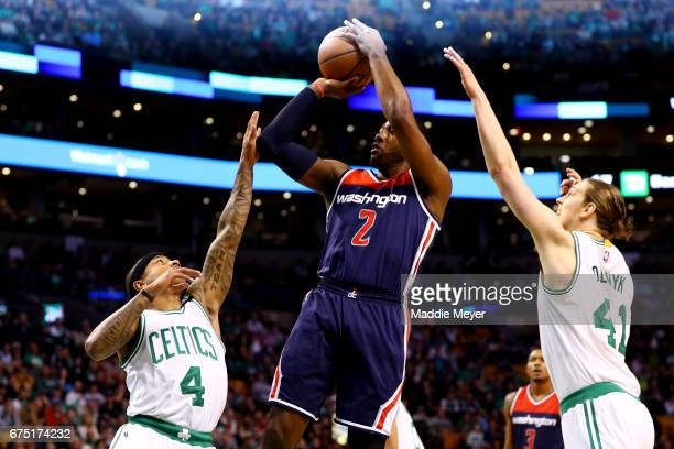 John Wall of the Washington Wizards takes a shot between Isaiah Thomas and Kelly Olynyk of the Boston Celtics during the first quarter of Game One of...