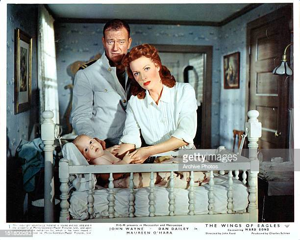 John Wayne and Maureen O'Hara stand over a baby in a crib in a scene from the film 'The Wings Of Eagles' 1957