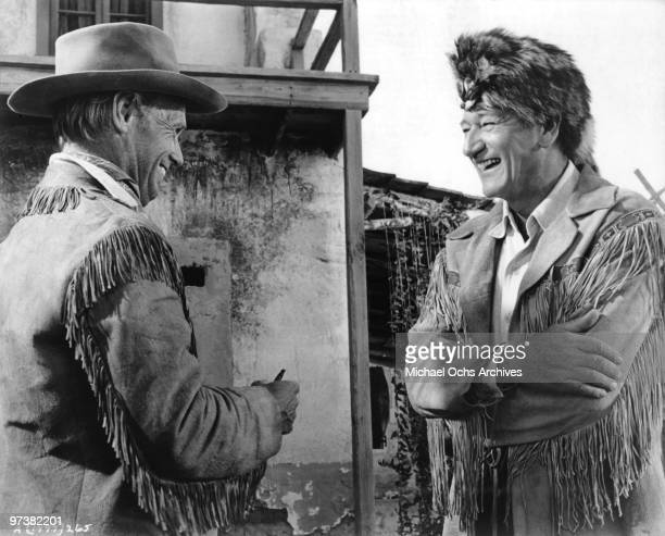 John Wayne chats with Richard Widmark on the set of his movie 'The Alamo' in 1960 at the Alamo Village he had built for the film in Brackettville...