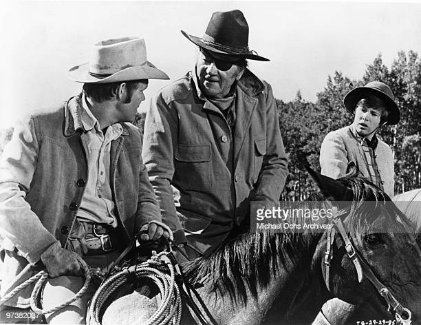 John Wayne in his Oscar winning performance as Rooster Cogburn in scene with Kim Darby and Glen Campbell from the movie 'True Grit' directed by Henry...