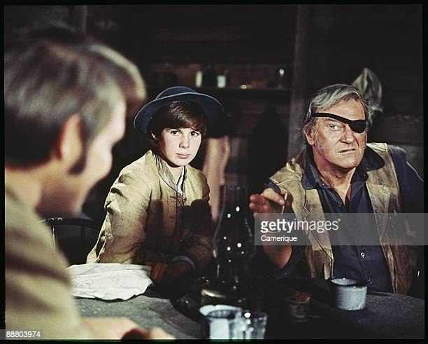 John Wayne points ominously at Glen Campbell while sitting next to the actress Kim Darby in this scene from the western 'True Grit' 1969
