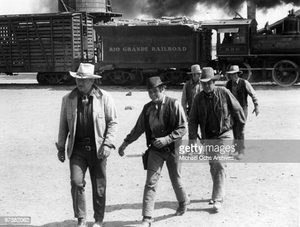 John Wayne Rod Taylor Ben Johnson Jerry Gatlin and Christopher George on the set of 'The Train Robbers' directed by Burt Kennedy in 1973 in Durango...