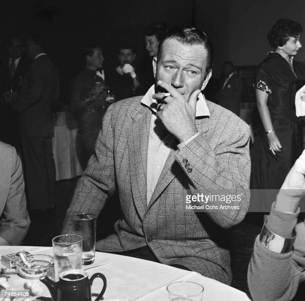 John Wayne smokes a cigarette at a party for Milton Berle on September 26 1955 in Los Angeles California