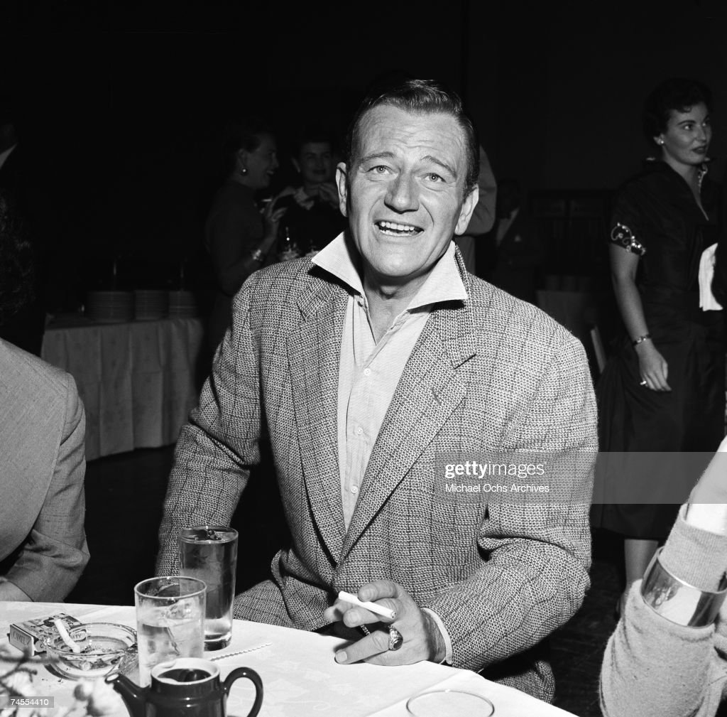 <a gi-track='captionPersonalityLinkClicked' href=/galleries/search?phrase=John+Wayne&family=editorial&specificpeople=69997 ng-click='$event.stopPropagation()'>John Wayne</a> smokes a cigarette at a party for Milton Berle on September 26 1955 in Los Angeles, California.