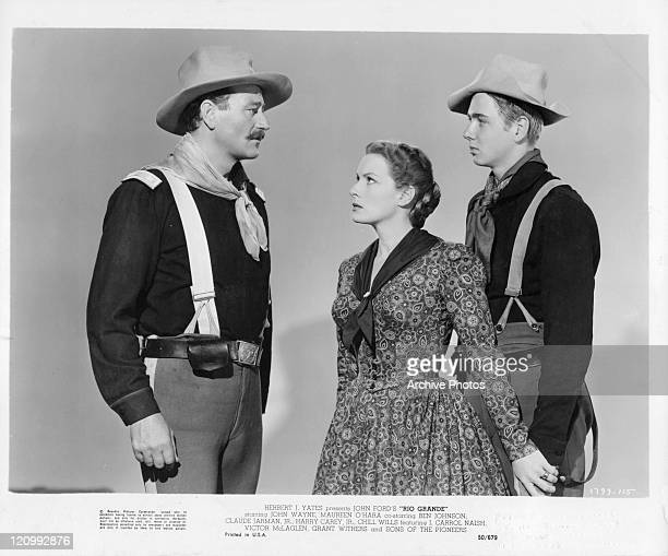 John Wayne stands in uniform looking upset while Maureen O'Hara stands in between him and a young boy protecting him in a scene from the film 'Rio...