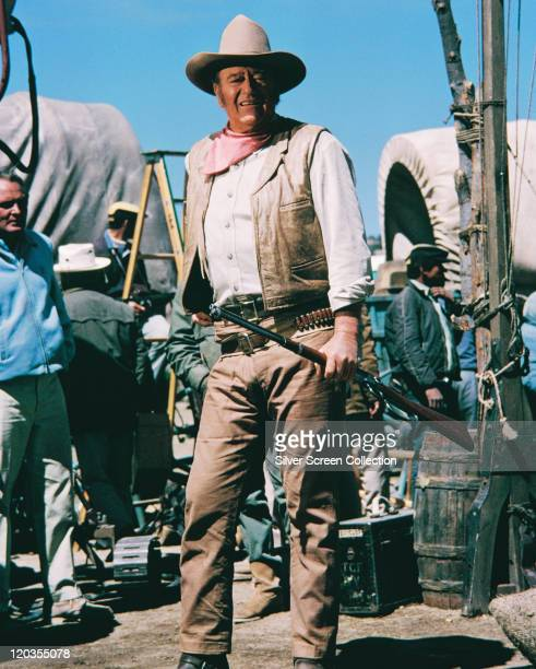 John Wayne US actor posing with a rifle in a publicity portrait on the set of the film 'The Undefeated' with covered wagons in the background USA...