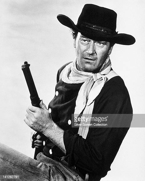 John Wayne US actor wearing a black cowboy hat and a white neckerchief holding a rifle in a studio portrait against a white background issued as...