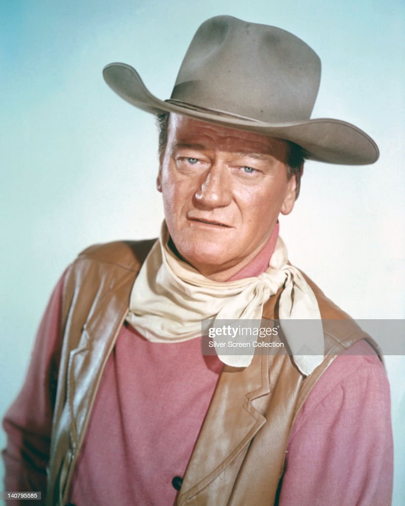 John Wayne (1907 - 1979), US actor wearing a tan leather waistcoat, a pink shirt and a white neckerchief, in a studio portrait, against a light blue background, circa 1970.