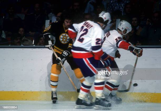 John Wensink of the Boston Bruins battles with Mike Bossy and Bryan Trottier of the New York Islanders on October 15 1977 at the Nassau Coliseum in...