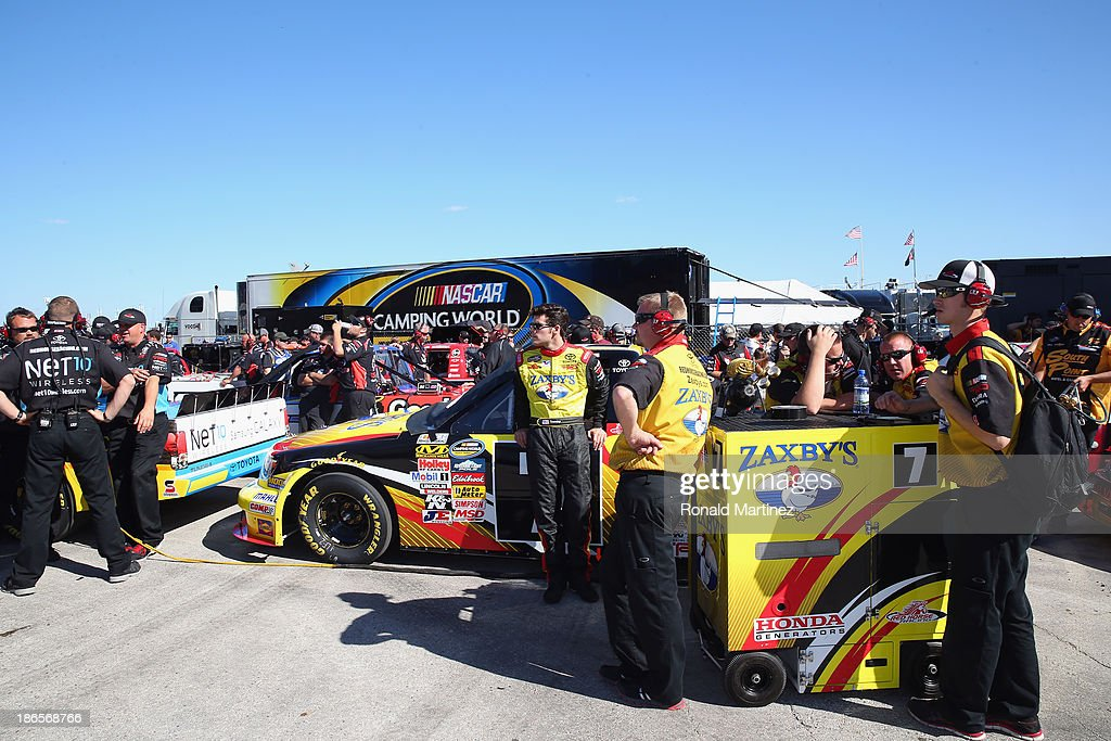 John Wes Townley, driver of the #7 Zaxby's Toyota, and his crew stand on the grid during qualifying for the NASCAR Camping World Truck Series WinStar World Casino 350k at Texas Motor Speedway on November 1, 2013 in Fort Worth, Texas.