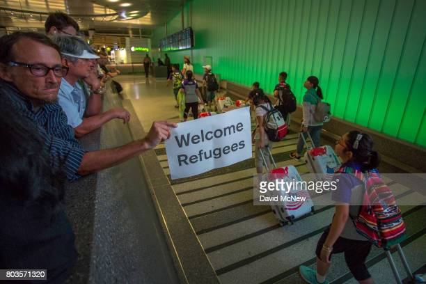 John Wider carries a welcome sign near arriving international travelers on the first day of the the partial reinstatement of the Trump travel ban...