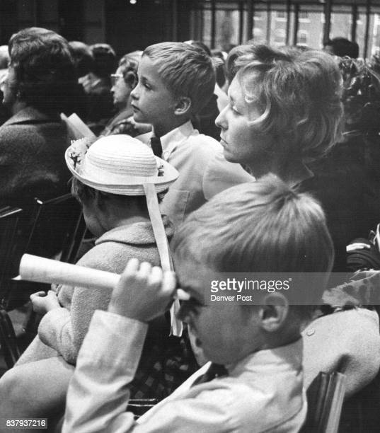 John Wiesner views the orchestra through a makeshift paper telescope while his sister Susan and his brother Tammy join his mother Mrs Patrick Wiener...