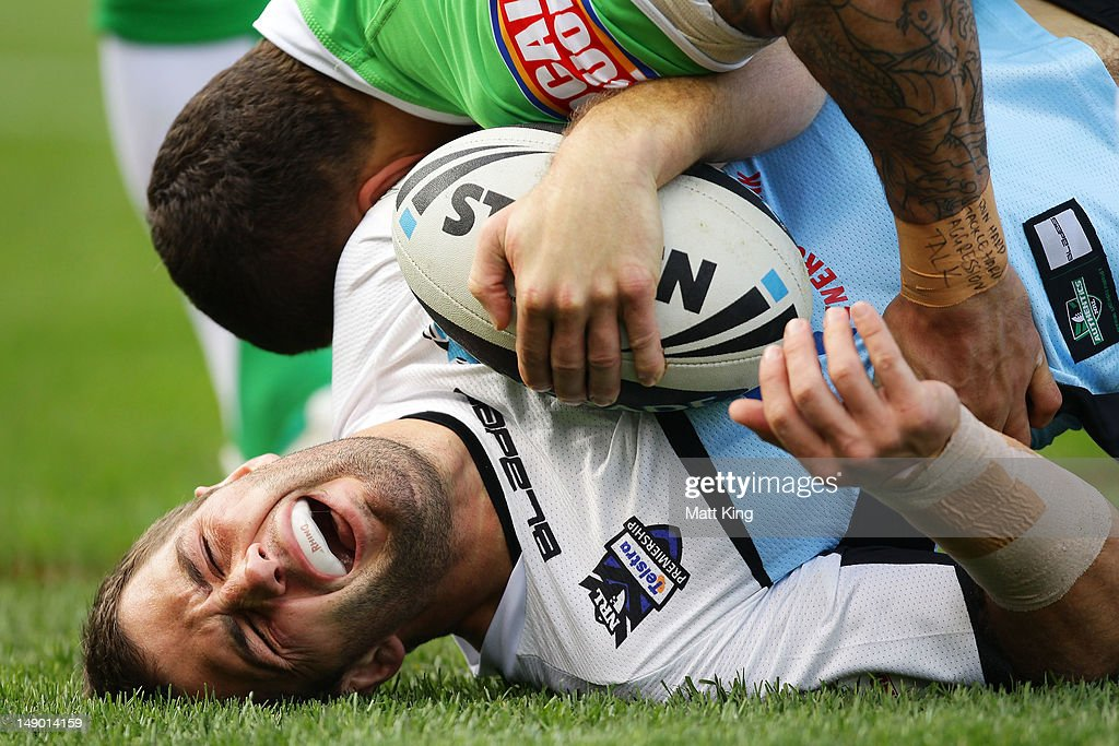 John Williams of the Sharks is tackled during the round 20 NRL match between the Cronulla Sharks and the Canberra Raiders at Toyota Stadium on July...