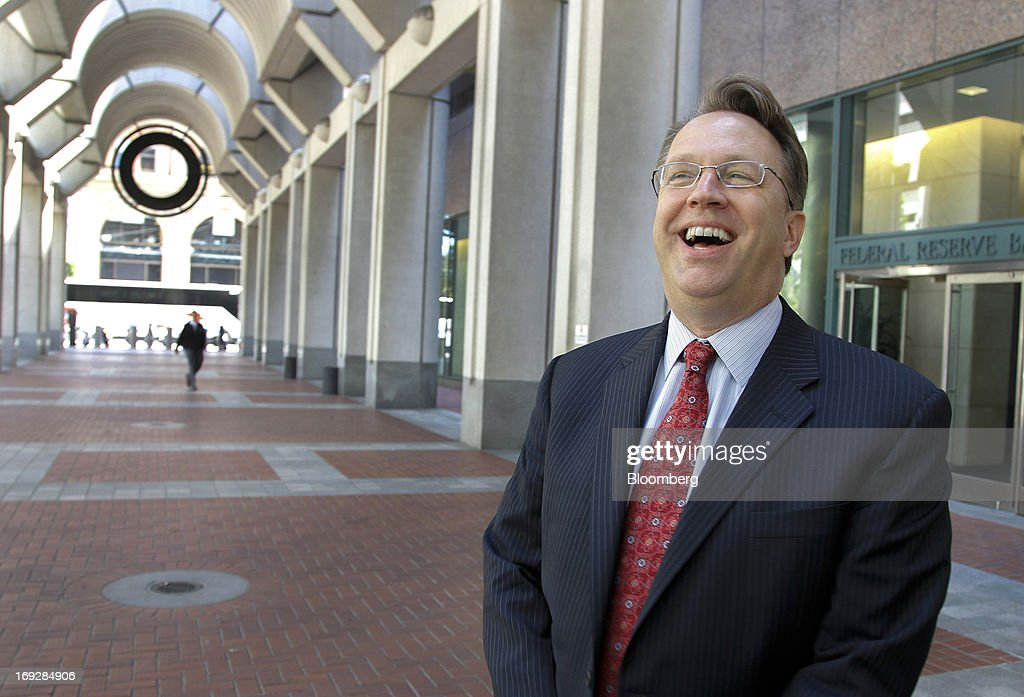 """John Williams, president and chief executive officer of the Federal Reserve Bank of San Francisco, laughs while standing for a photograph outside the Federal Reserve Bank in San Francisco, California, U.S., on Wednesday, May 22, 2013. Williams favors a reduction in quantitative easing """"perhaps as early as this summer."""" Photographer: Tony Avelar/Bloomberg via Getty Images"""