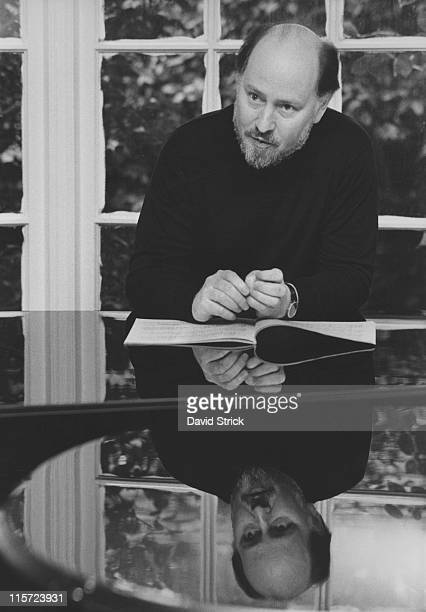 John Williams US composer conductor and pianist inspecting a book of sheet music on top of a grand piano at this home in Los Angeles California USA...