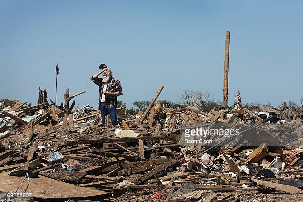 John Wilson surveys the neighborhood from atop the rubble that was once a home that his son and exwife shared before the home and the neighborhood...