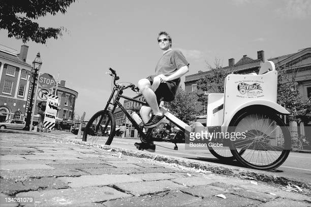 John Wright owner of and peddler for Granite State Pedicabs is photographed on the corner of Market and Pleasant Streets in Portsmouth NH on Saturday...