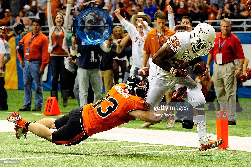 Johnathan Gray #32 of the University of Texas Longhorns scores on Rueben Robinson #13 of the Oregon State Beavers during the Valero Alamo Bowl at the Alamodome on December 29, 2012 in San Antonio, Texas. Texas won the game 31-27.