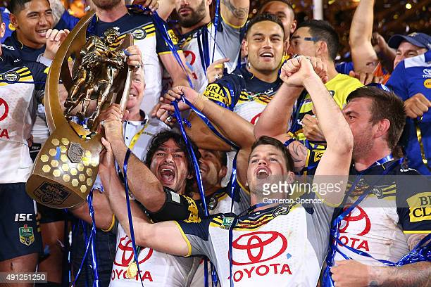 Johnathan Thurston and Lachlan Coote of the Cowboys hold aloft the premiership trophy after winning the 2015 NRL Grand Final match between the...