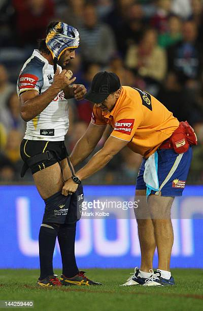 Johnathan Thurston of the Cowboys has his pants pulled up by a trainer during the round 10 NRL match between the Newcastle Knights and the North...