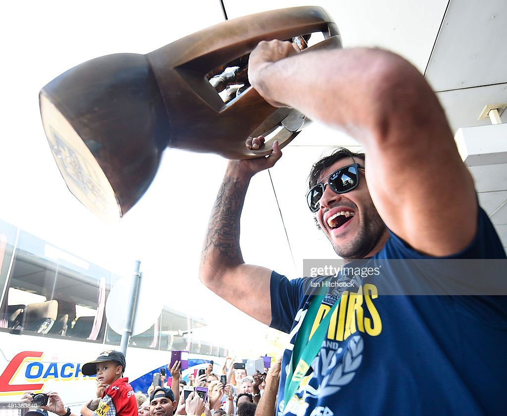 Johnathan Thurston of the Cowboys is hoisted onto the shoulders of Ben Hannant and Kane Linnett with the NRL trophy after arriving back at the Townsville airport before heading out to the North Queensland Cowboys NRL Grand Final fan day at 1300 Smiles Stadium on October 5, 2015 in Townsville, Australia.