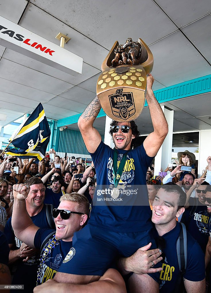 Johnathan Thurston of the Cowboys is hoisted onto the shulders of Ben Hannant and Kane Linnett with the NRL trophy after arriving back at the Townsville airport before heading out to the North Queensland Cowboys NRL Grand Final fan day at 1300 Smiles Stadium on October 5, 2015 in Townsville, Australia.