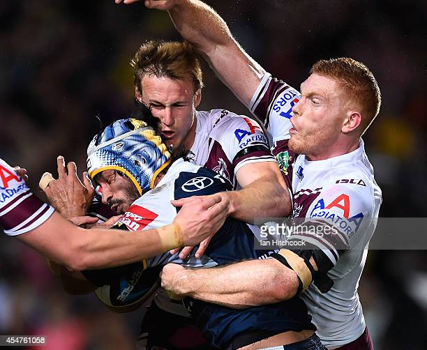 Johnathan Thurston of the Cowboys is tackled by Daly CherryEvans and Tom Symonds of the Sea Eagles during the round 26 NRL match between the North...