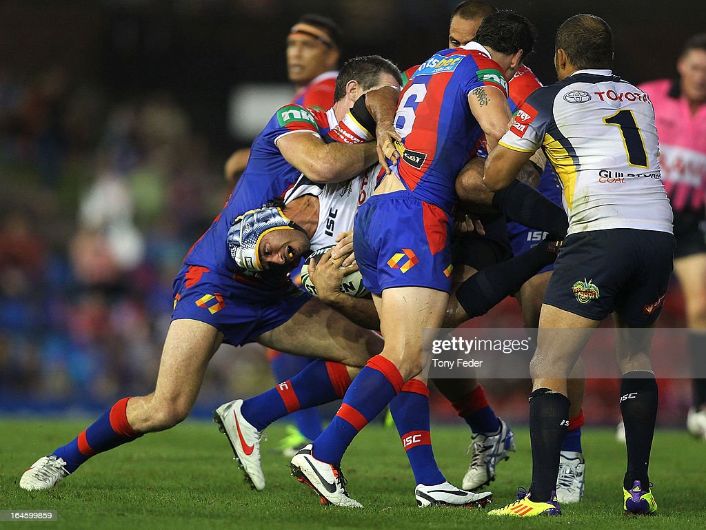 <a gi-track='captionPersonalityLinkClicked' href=/galleries/search?phrase=Johnathan+Thurston&family=editorial&specificpeople=233427 ng-click='$event.stopPropagation()'>Johnathan Thurston</a> of the Cowboys is tackled by the Knights defense during the round three NRL match between the Newcastle Knights and the North Queensland Cowboys at Hunter Stadium on March 25, 2013 in Newcastle, Australia.